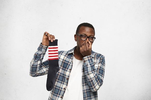 Afroamerykanin hipster szczypiący nos z powodu nieprzyjemnego zapachu brudnej, śmierdzącej skarpetki w dłoni