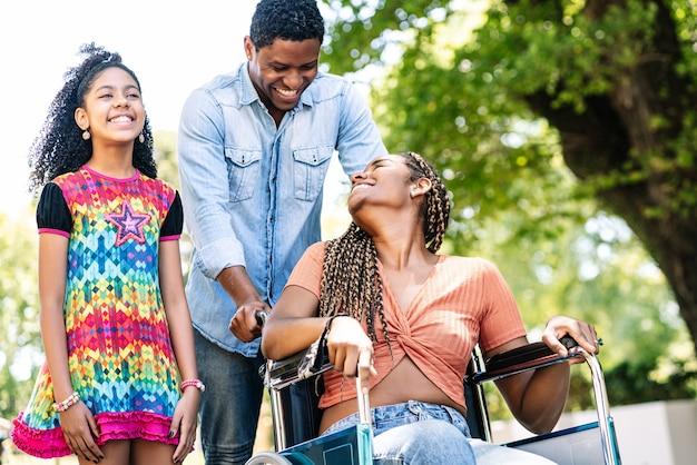 Afroamerykanin kobieta na wózku inwalidzkim, spacerująca z córką i mężem na świeżym powietrzu.