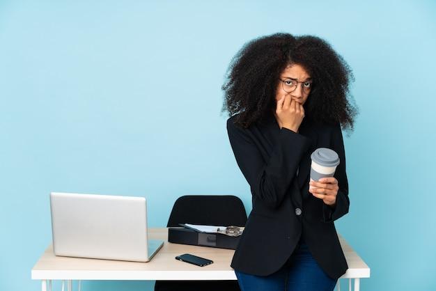 Afroamerykanin kobieta pracuje w swoim miejscu pracy, mając wątpliwości