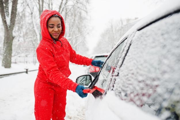 Afroamerykanin kobieta w czerwonej bluzie z kapturem czysty samochód od śniegu w zimowy dzień.