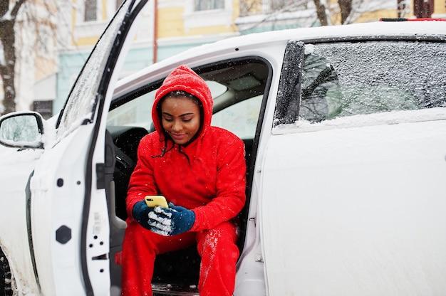 Afroamerykanin kobieta w czerwonej bluzie z kapturem siedzi w samochodzie w śnieżny zimowy dzień z telefonem komórkowym.
