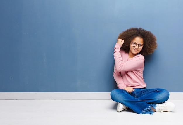 Afroamerykanin mała dziewczynka czuje się szczęśliwa, zadowolona i silna, wyginając się i muskularny biceps, wyglądając silnie po siłowni na podłodze