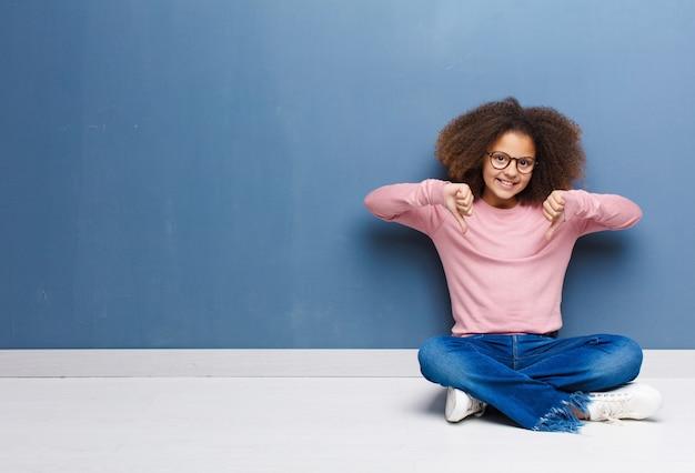 Afroamerykanin mała dziewczynka wygląda smutno, rozczarowana lub wściekła, pokazuje kciuk w dół w nieporozumieniu, czuje się sfrustrowana siedząc na podłodze