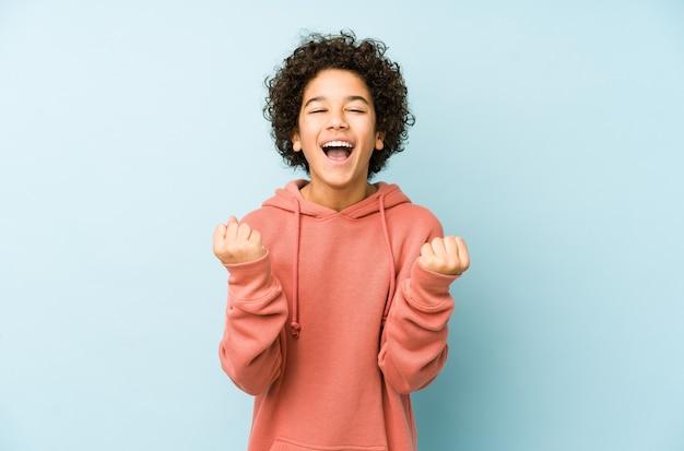 Afroamerykanin mały chłopiec na białym tle doping beztroski i podekscytowany. koncepcja zwycięstwa.
