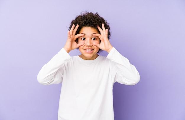 Afroamerykanin mały chłopiec na białym tle, mając otwarte oczy, aby znaleźć szansę na sukces.