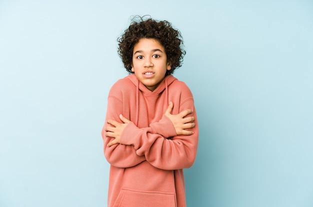Afroamerykanin mały chłopiec na białym tle marznie z powodu niskiej temperatury lub choroby.
