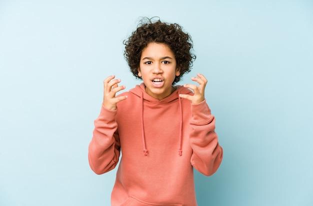 Afroamerykanin mały chłopiec na białym tle zdenerwowany krzyczy z napiętymi rękami.