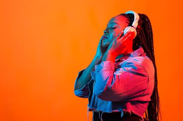 Afroamerykanin, młoda kobieta, słuchanie muzyki online, taniec i śpiew przez słuchawki, neon
