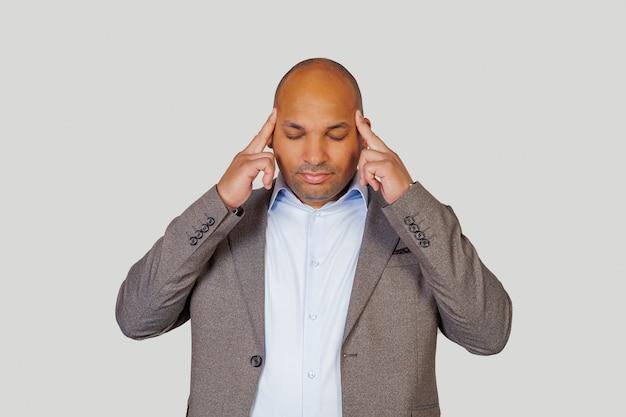 Afroamerykanin młody człowiek masuje whisky palcami, starając się skoncentrować na pracy
