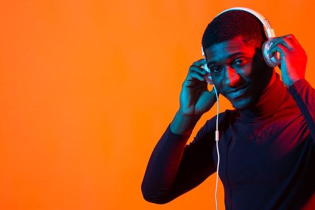 Afroamerykanin, młody człowiek, słuchanie muzyki online, taniec i śpiew przez słuchawki, światło neonowe