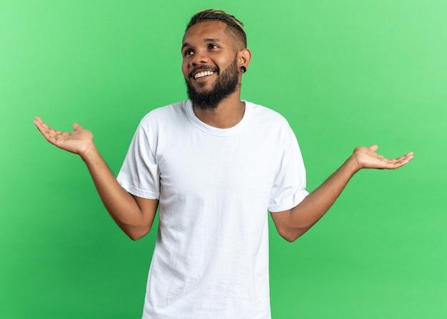 Afroamerykanin, młody człowiek w białej koszulce, patrzący na bok, uśmiechający się szeroko rozpostartymi ramionami na boki, stojący na zielonym tle