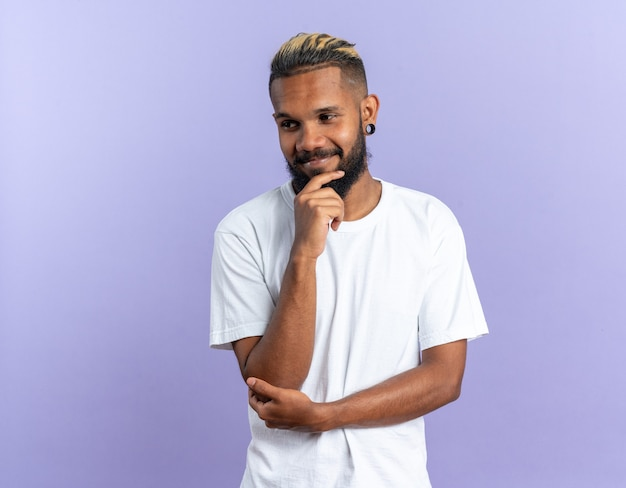 Afroamerykanin, młody człowiek w białej koszulce, patrzący na bok z ręką na brodzie, uśmiechnięty pewnie stojący na niebieskim tle