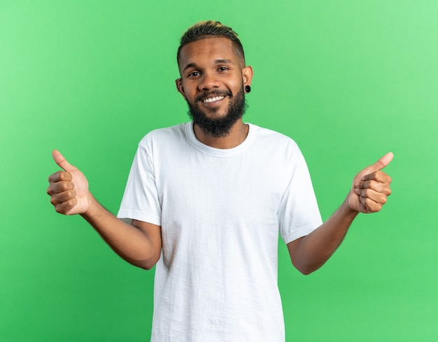 Afroamerykanin młody człowiek w białej koszulce patrzący na kamerę szczęśliwy i wesoły uśmiechnięty szeroko broad