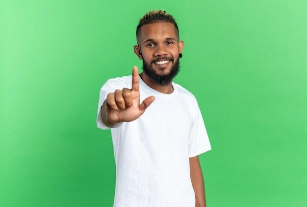 Afroamerykanin młody człowiek w białej koszulce patrzący na kamerę z dużym uśmiechem