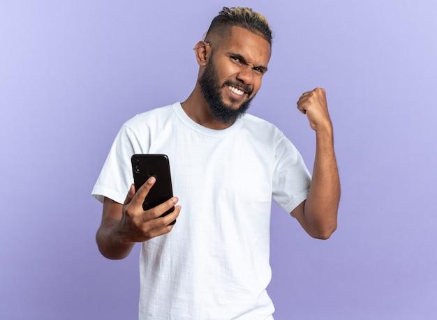 Afroamerykanin, młody człowiek w białej koszulce, trzymając smartfon, zaciskając pięść, szczęśliwy i podekscytowany, ciesząc się swoim sukcesem, stojąc na niebieskim tle