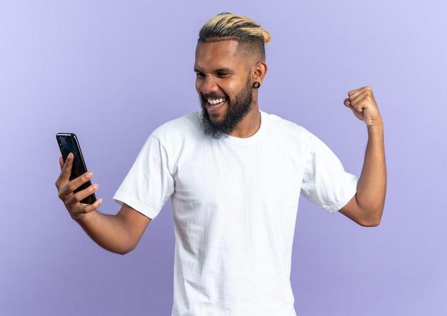 Afroamerykanin, młody człowiek w białej koszulce, trzymając smartfona, zaciskając pięść, szczęśliwy i podekscytowany, ciesząc się jego sukcesem, stojąc na niebieskim tle