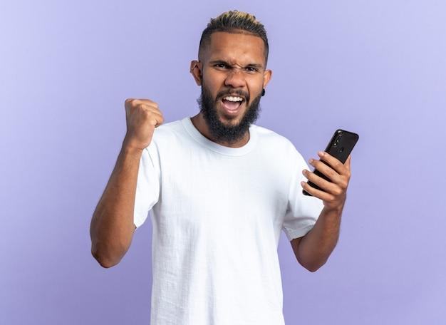 Afroamerykanin, młody człowiek w białej koszulce, trzymając smartfona, zaciskając pięść, szczęśliwy i podekscytowany, krzycząc ciesząc się swoim sukcesem, stojąc na niebieskim tle