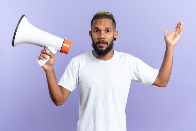 Afroamerykanin młody człowiek w białej koszulce trzymającej megafon