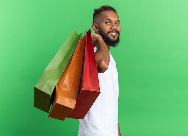 Afroamerykanin młody człowiek w białej koszulce trzymający papierowe torby patrzący na kamerę uśmiechający się radośnie szczęśliwy i pozytywny