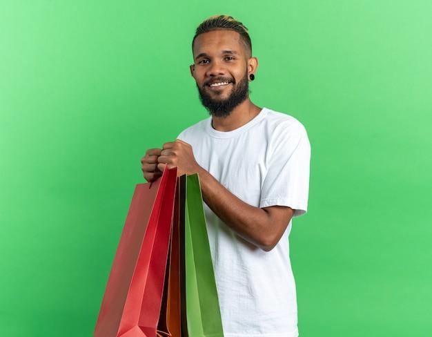Afroamerykanin, młody człowiek w białej koszulce, trzymający papierowe torby, patrzący na kamerę, uśmiechający się radośnie