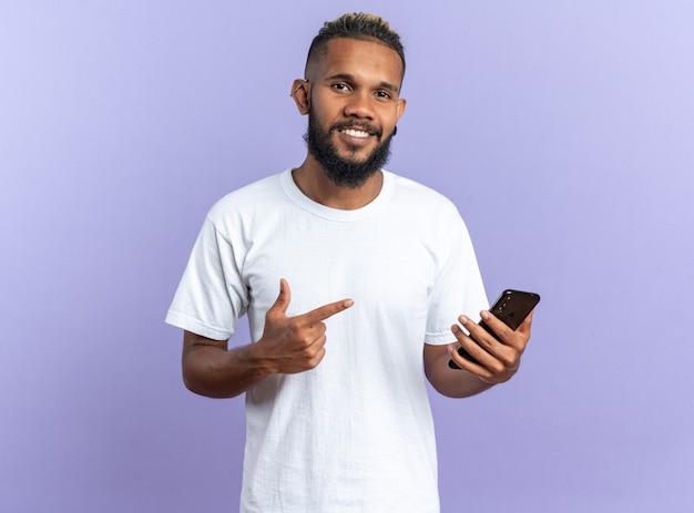 Afroamerykanin, młody człowiek w białej koszulce, trzymający smartfon wskazujący