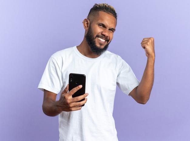 Afroamerykanin, młody człowiek w białej koszulce, trzymający smartfona, zaciskając pięść szczęśliwy