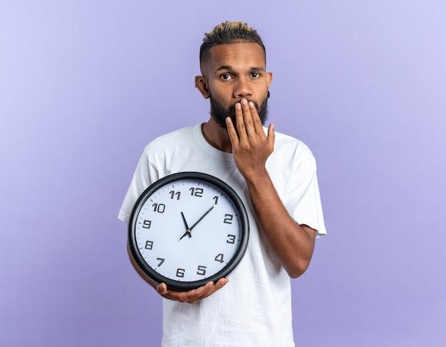 Afroamerykanin, młody człowiek w białej koszulce, trzymający zegar ścienny, patrzący na aparat, który jest zszokowany zasłaniając usta