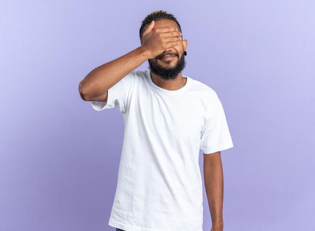 Afroamerykanin, młody człowiek w białej koszulce, zamykający oczy ręką stojącą na niebieskim tle