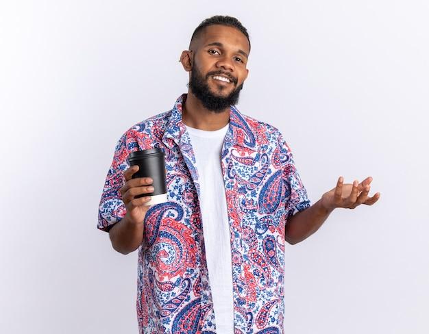 Afroamerykanin młody człowiek w kolorowej koszuli patrzący w kamerę uśmiechający się radośnie trzymający papierowy kubek stojący nad białymi