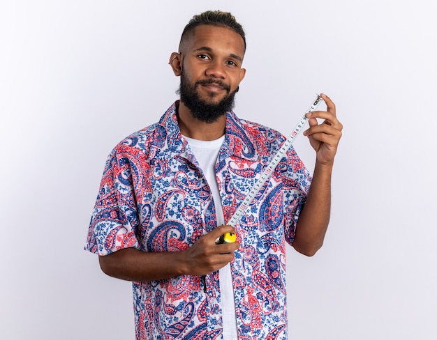 Afroamerykanin młody człowiek w kolorowej koszuli trzymającej taśmę mierniczą patrząc na kamerę z uśmiechem na twarzy szczęśliwa i pozytywna pozycja na białym tle