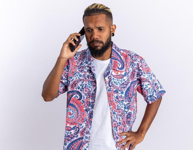 Afroamerykanin młody człowiek w kolorowej koszuli wyglądający na zdezorientowanego i bardzo zaniepokojonego