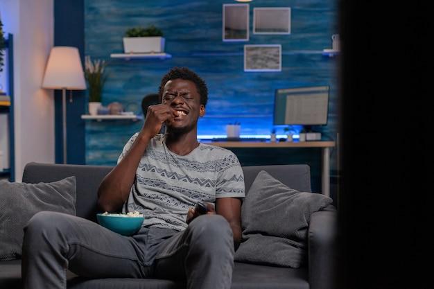 Afroamerykanin, młody dorosły, śmiejąc się podczas filmu komediowego, patrząc na telewizję