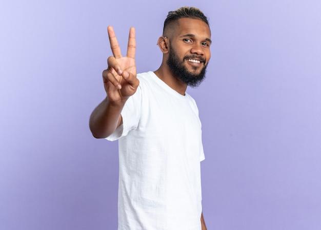 Afroamerykanin młody mężczyzna w białej koszulce patrzący na kamerę uśmiechający się pewnie pokazując numer trzy showing