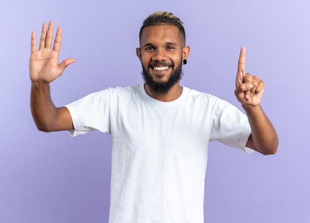 Afroamerykanin młody mężczyzna w białej koszulce patrzący na kamerę uśmiechający się radośnie pokazując cyfrę sześć palcami