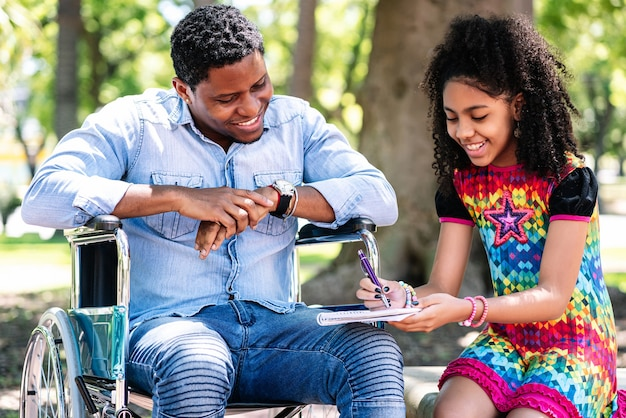 Afroamerykanin na wózku inwalidzkim, ciesząc się i bawiąc się z córką w parku.