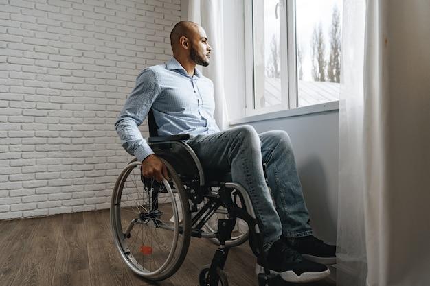 Afroamerykanin na wózku inwalidzkim siedzi samotnie przy oknie w domu