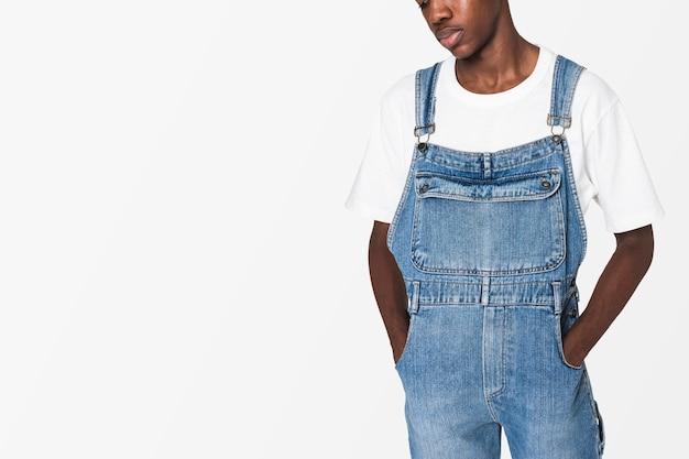 Afroamerykanin nastolatek chłopiec w dżinsowych ogrodniczkach streetwear strzelać do odzieży