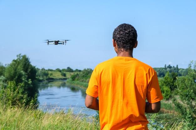 Afroamerykanin obsługujący drona z kontrolerem na łące z plecami