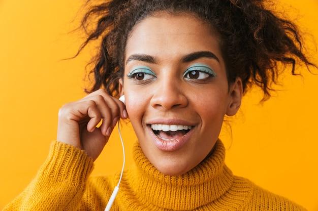 Afroamerykanin Optymistyczna Kobieta W Ubranie, Słuchanie Muzyki Przez Białe Słuchawki, Na Białym Tle Premium Zdjęcia