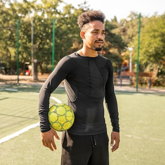 Afroamerykanin pozowanie z piłką nożną na boisku