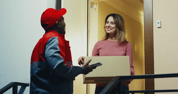 Afroamerykanin, pracownik firmy transportowej w niebieskim stroju, stojący przy drzwiach i wręczający skrzynkę pocztową uśmiechniętej, dobrze wyglądającej kobiecie rasy białej.