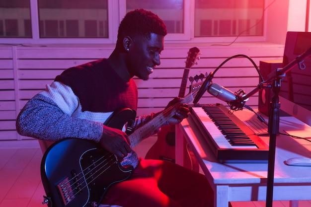 Afroamerykanin profesjonalny muzyk nagrywający gitarę basową w cyfrowym studio w domu, muzyka