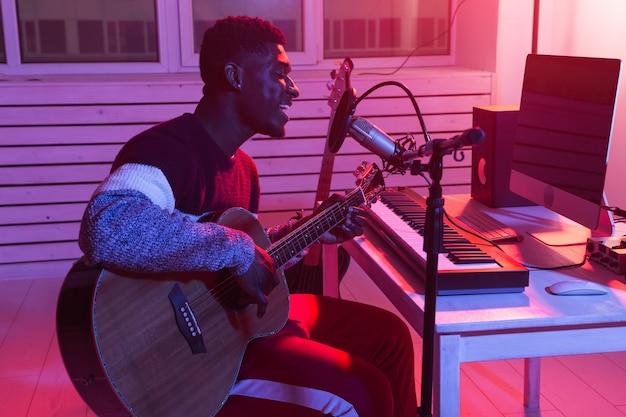 Afroamerykanin profesjonalny muzyk nagrywający gitarę w cyfrowym studio w domu, produkcja muzyczna