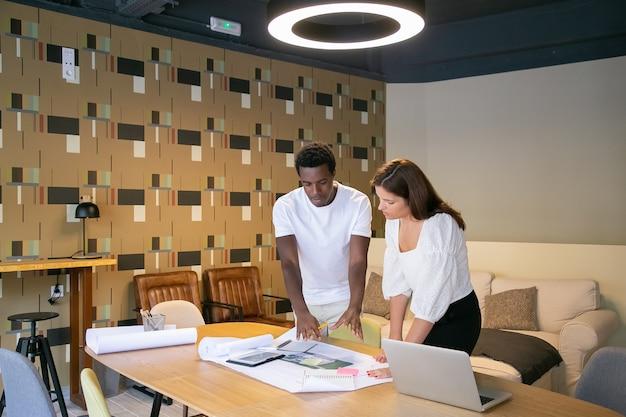 Afroamerykanin projektant objaśnia projekt klientowi i pokazuje szkic