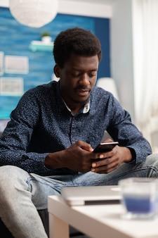Afroamerykanin przeglądający media społecznościowe za pomocą smartfona
