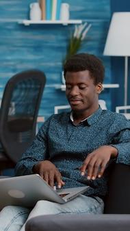 Afroamerykanin przeglądający za pomocą laptopa przeszukującego media społecznościowe