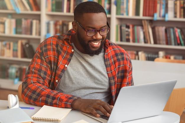 Afroamerykanin przygotowuje się do egzaminu w bibliotece