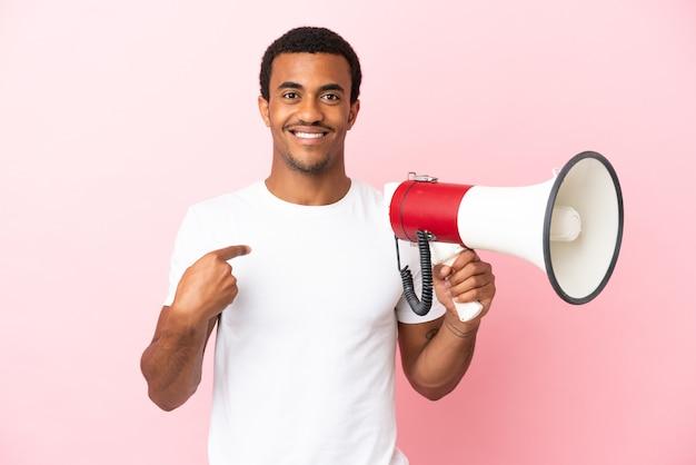 Afroamerykanin, przystojny mężczyzna na białym tle, trzymający megafon i z niespodzianką wyrazem twarzy