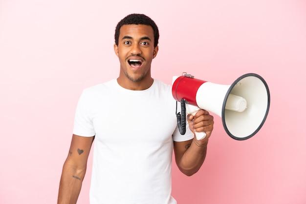 Afroamerykanin, przystojny mężczyzna na izolowanym różowym tle, trzymający megafon i z wyrazem zaskoczenia