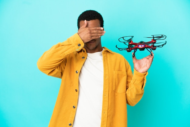 Afroamerykanin przystojny mężczyzna trzyma drona na na białym tle niebieskim tle zasłaniając oczy rękami. nie chcę czegoś widzieć